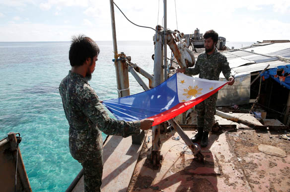 Philippine Marines fold a Philippine national flag during a flag retreat at the BRP Sierra Madre, a marooned transport ship in the disputed Second Thomas Shoal, part of the Spratly Islands in the South China Sea, March 29, 2014. (Erik De Castro/Reuters)