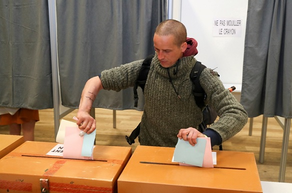 A man votes with ripped up ballots during the Belgian general and regional elections, and for the European Parliament elections in Limal, Belgium, on May 26, 2019. (Yves Herman/Reuters)