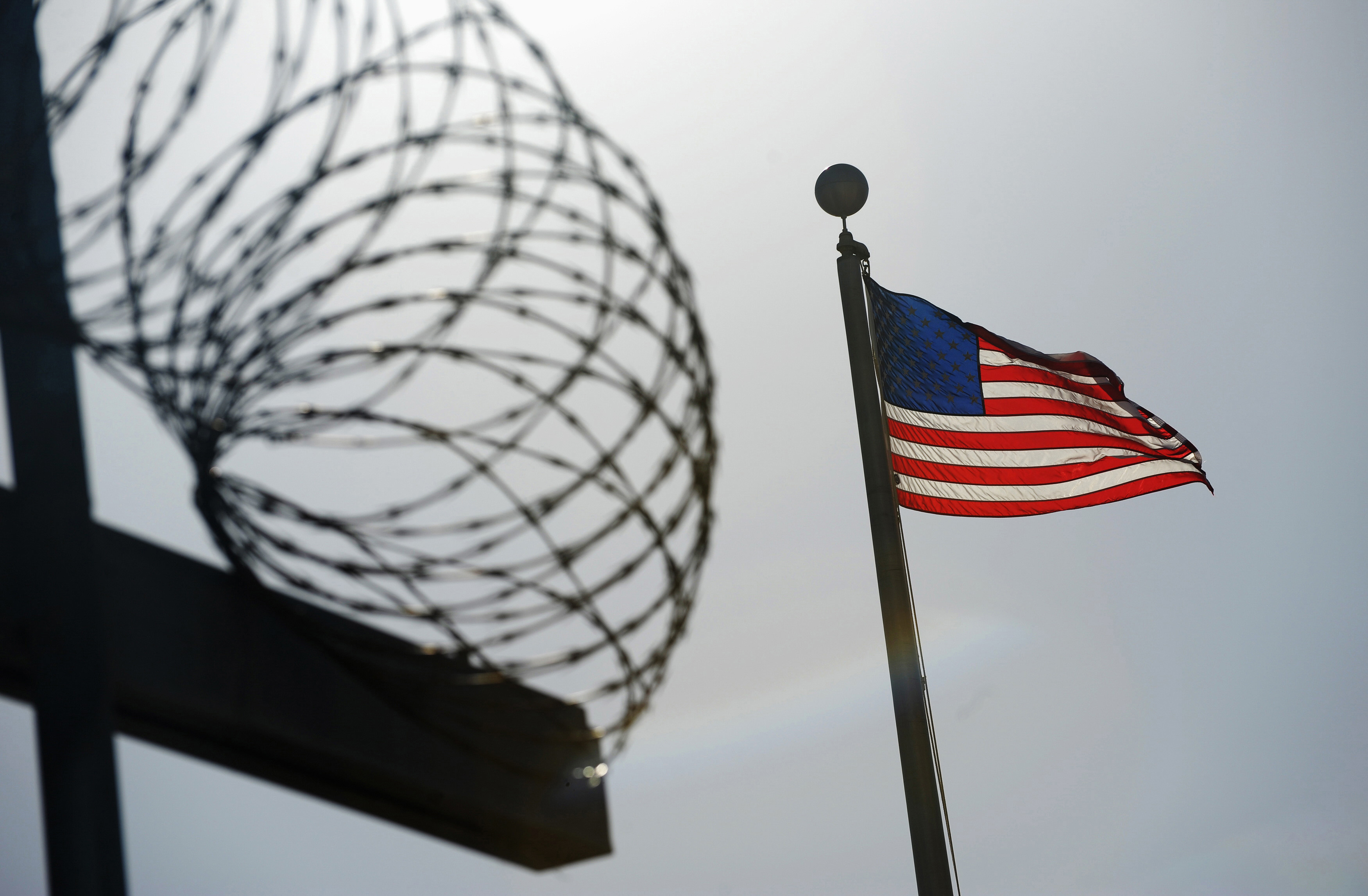 A U.S. flag flies above a razorwire-topped fence at the U.S. Naval Station Guantanamo Bay on December 10, 2008. REUTERS/Mandel Ngan/Pool (CUBA)